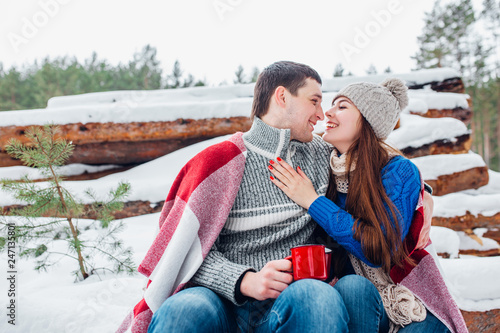 Young Romantic Couple With Hot Drink In Winter Forest Couple In