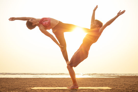 Two people practicing yoga in the sunset light on goa india beach. female and male acro yogi tantra flying copyspce