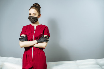 Portrait of young asian woman in medical uniform and black mask and gloves on grey background