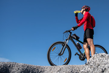 Cyclist resting and drinking isotonic drink. Backlight, sunny summer day. Extreme mountain bike...