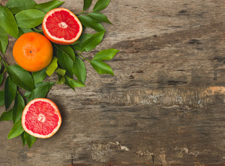 juicy, healthy grapefruit lies on an old, vintage wooden background with green twigs