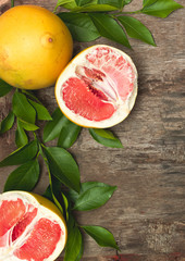 juicy, healthy grapefruit, pomelo lies on an old, vintage wooden background with green twigs