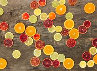 many different juicy and healthy citrus fruits lie together on an old, vintage wood background