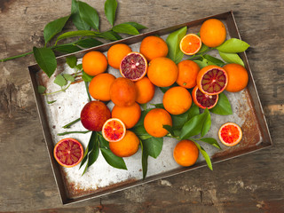fresh, juicy blood oranges lie in an old silver pan on a wooden background