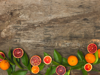 fresh, juicy oranges and blood oranges lie on an old wooden background