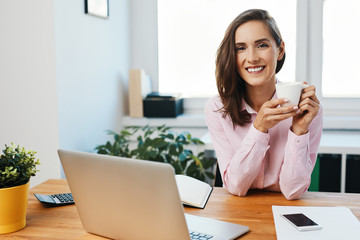 Portrait of young woman sitting at desk in office and drinking coffee