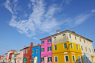 Venice, Burano island canal, small colored houses and the boats