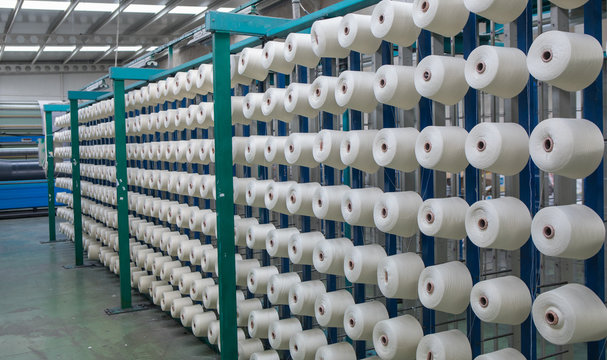 Group of bobbin thread cones on a warping machine in a textile mill. Yarn ball making in a textile factory. Textile industry - yarn spools on spinning machine in a textile factory