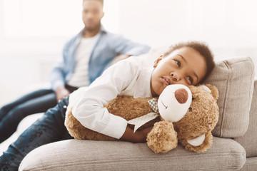 Upset little girl hugging teddy bear on sofa