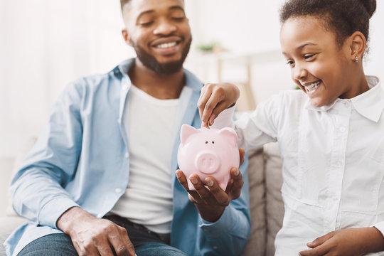 Little african-american girl saving money to piggybank