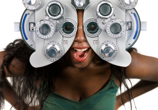 young and happy black afro American woman at hospital looking through optometric hospital device checking eyes having sight exam in ophthalmology health care
