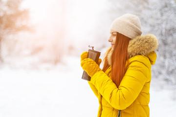 Cute girl enjoying coffee on a winter day.