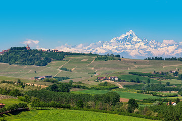 Green hills and snowy mountain peak on background in Italy.