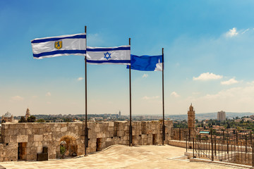 Three flags waiving on top of the citadel walls in Jerusalem.
