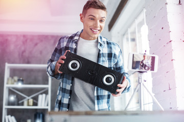 Blue-eyed handsome student feeling cheerful after receiving loudspeakers