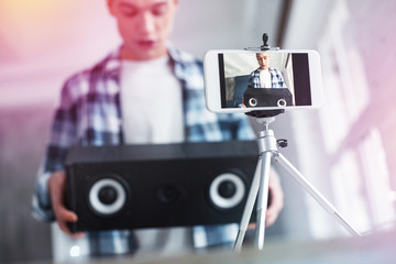 Handsome student filming video about birthday presents using photo stand