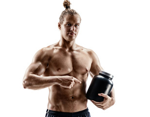 Sportsman holds large bank with protein nutrition in hand. Photo of muscular man with naked torso points to jar of sports nutrition on white background