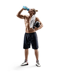 Strong man drinks protein cocktail after training. Photo of sportsman with big jar of sports nutrition isolated on white background. Resting time. Full length