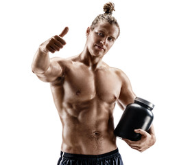 Sportsman holds big jar with sports nutrition and shows thumb up. Photo of muscular man with naked torso on white background.