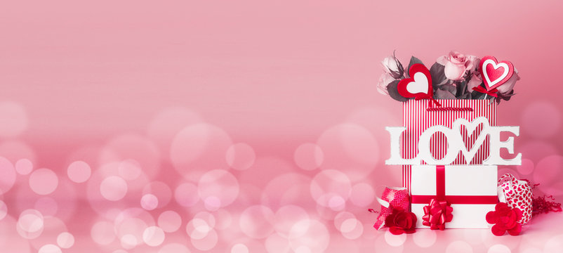 Valentines day composing with gift box, roses bunch and hearts in shopping bag, word Love and ribbons standing at red pink background with bokeh, front view, banner