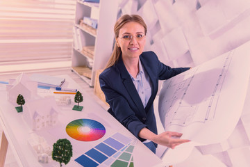 Pleasant female architect verifying blueprint at office