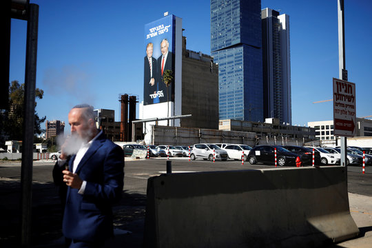 A man smokes an e-cigarette as a Likud election campaign billboard, depicting U.S. President Donald Trump shaking hands with Israeli Prime Minister Benjamin Netanyahu, is seen in the background at a main entrance to Tel Aviv, Israel