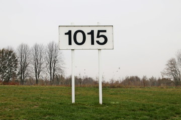 Distance sign for ships in kilometers at 1015 km on river Rhine in the Netherlands