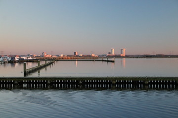 Sunset is reflecting over the water of the marina of the Rottemeren and river Rotte at Zevenhuizen with Nesselande district of Rotterdam as skyline in the Netherlands