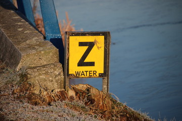 Yellow warning sign with letter 'Z' to warn that a water pipe have sunken on the bottom of the canal.