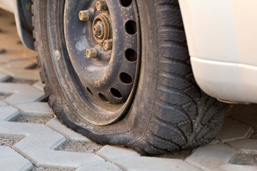 Flat tire of car on pavement. Side view outdoors of vehicle close up. Transportation problem, accident and insurance concept.