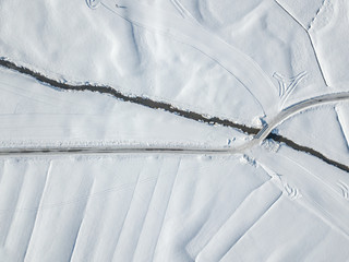 Aerial view of snow covered plain with brook flowing in straight line through landscape.