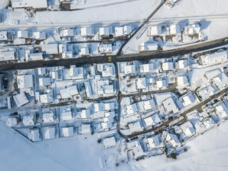 Aerial view of town with snow covered houses. Roof tops with snow on residential buildings in Switzerland.