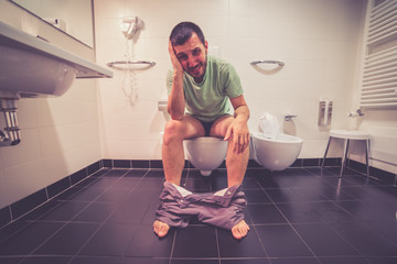 Young man suffering from diarrhea sit on toilet bowl at home