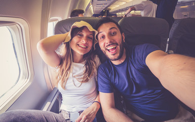 Young handsome couple taking a selfie on the airplane during flight around the world. They are a man and a woman, smiling and looking at camera. Travel, happiness and lifestyle concepts. Wall mural
