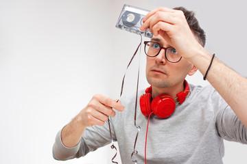 Mężczyzna naprawia kasetę magnetofonową.