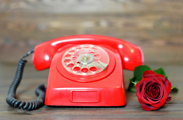 Vintage telephone and red rose