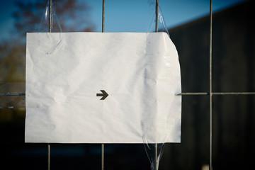 Blatt Papier mit einem Richtungspfeil an einem Zaun