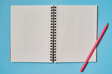 Open spiral blank notebook and pink pencil isolated on blue background, copy space for mockup. Still life, business, office, education concept. Top view, flatlay