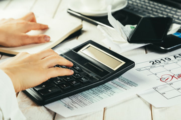 Tax day concept - calculator, calendar, tax form, hands, wood background
