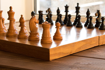 Chessboard with figures on a wooden table. Selective focus.