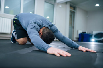 Low angle image of muscular man stretching back indoors.