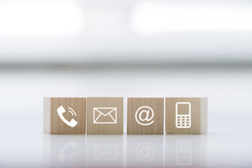 Contact us concept with wood block symbol telephone, mail, address and mobile phone. Website page contact us or e-mail marketing concept
