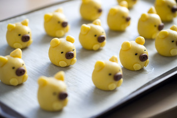 Cute yellow pig cookie on tray ready to be baked