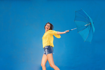 Cute teenage girl with brown hair and eyeglasses wearing yellow blouse and denim shorts while running with blue umbrella with black dots. Blue background.