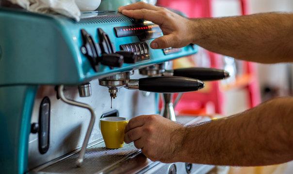 men's hands doing espresso in a cafe
