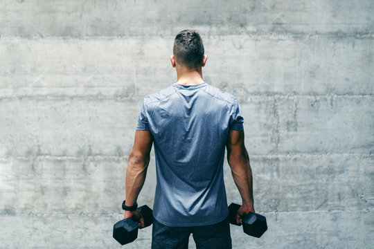 Dedicated bodybuilder in sportswear standing in front of the wall and holding dumbbells in hands, backs turned.