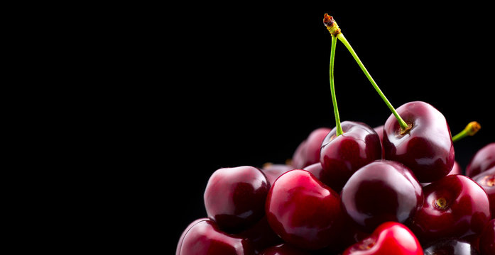 Cherry closeup. Organic ripe cherries isolated on black background