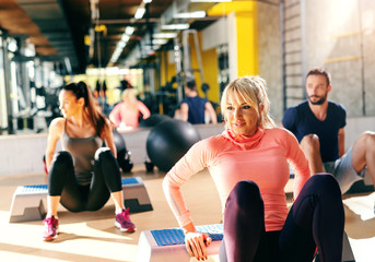 Group of dedicated people doing exercises on stepper in gym. In background their reflection in mirror.