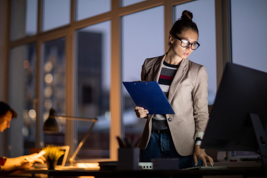 Young attractive businesswoman bending over workplace while looking at computer screen during work