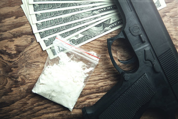 Pistol, money and packet of drugs on wooden background.